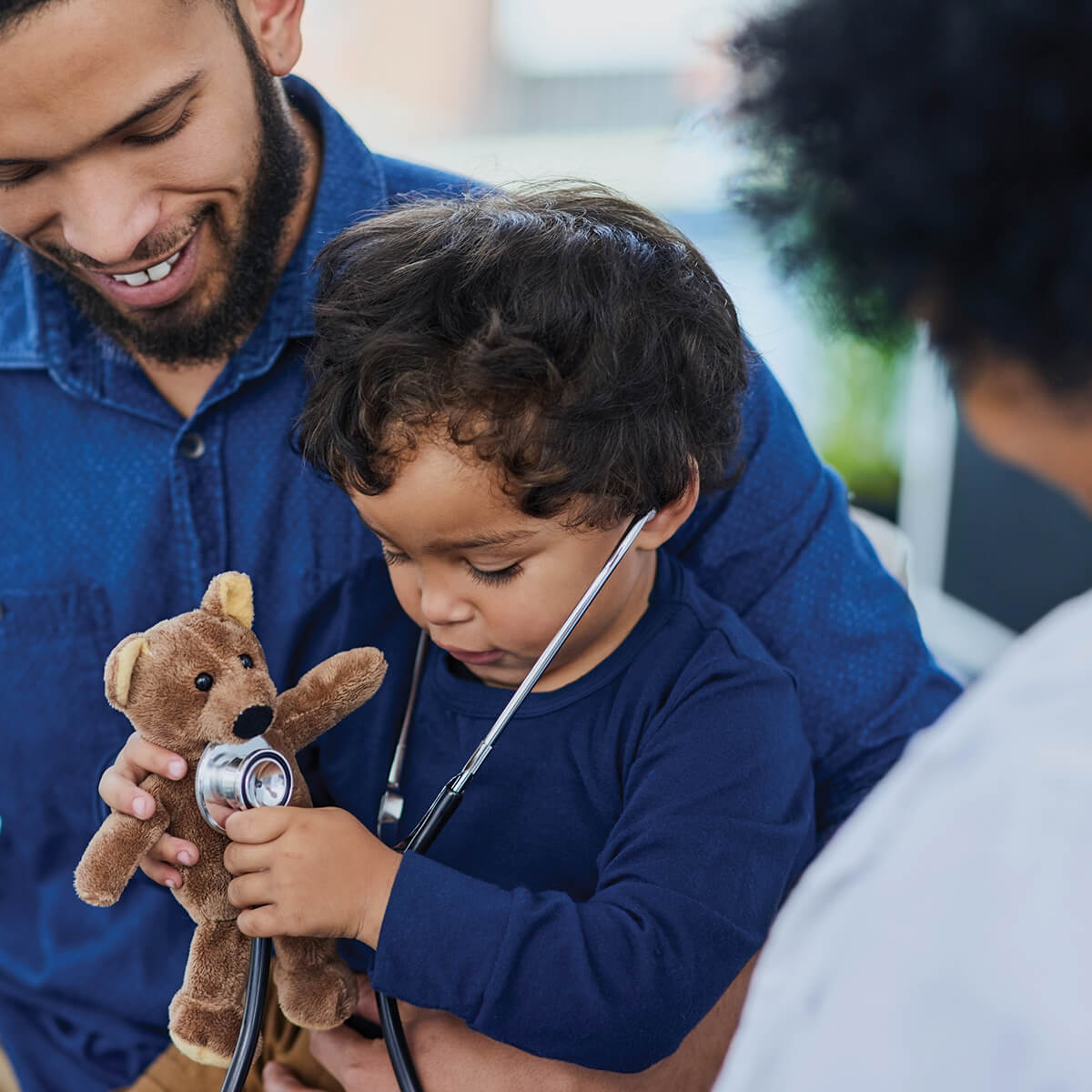 A father sitting with his son at the doctor's office, while the son tries to listen to a teddy bear's chest with a stethoscope